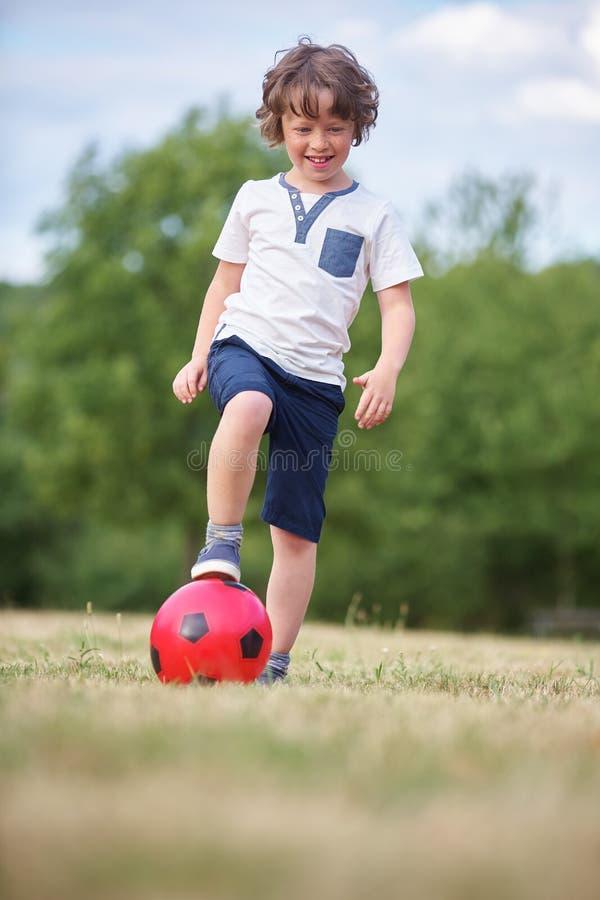 Glücklicher Junge mit einer Fußballkugel lizenzfreie stockfotos