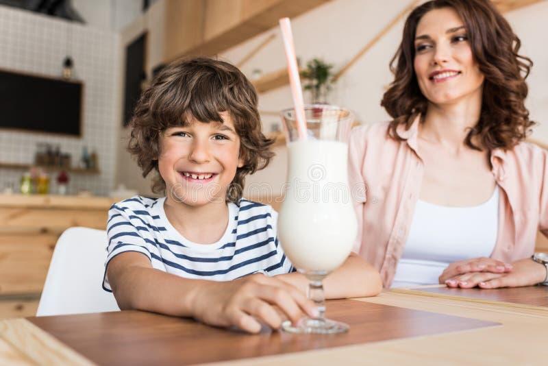 glücklicher Junge mit Glas Milchshaken und seiner lächelnden Mutter verwischt stockbild