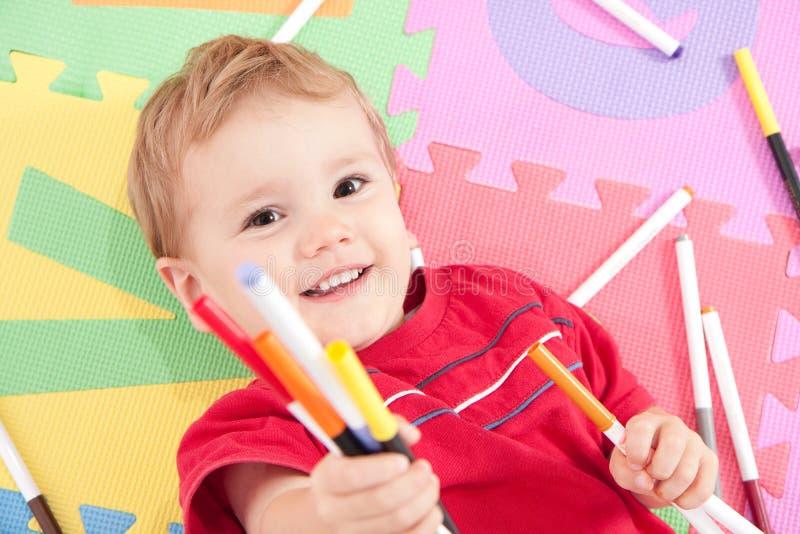Glücklicher Junge mit Kindzeichnungsfedern lizenzfreies stockfoto