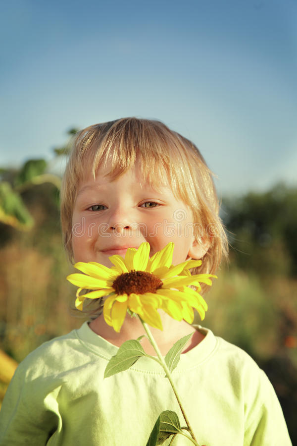 Glücklicher Junge mit Sonnenblume lizenzfreie stockfotografie