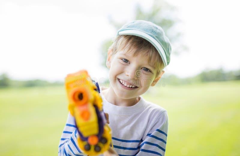 Glücklicher Junge mit Spielzeugwaffe stockfotos