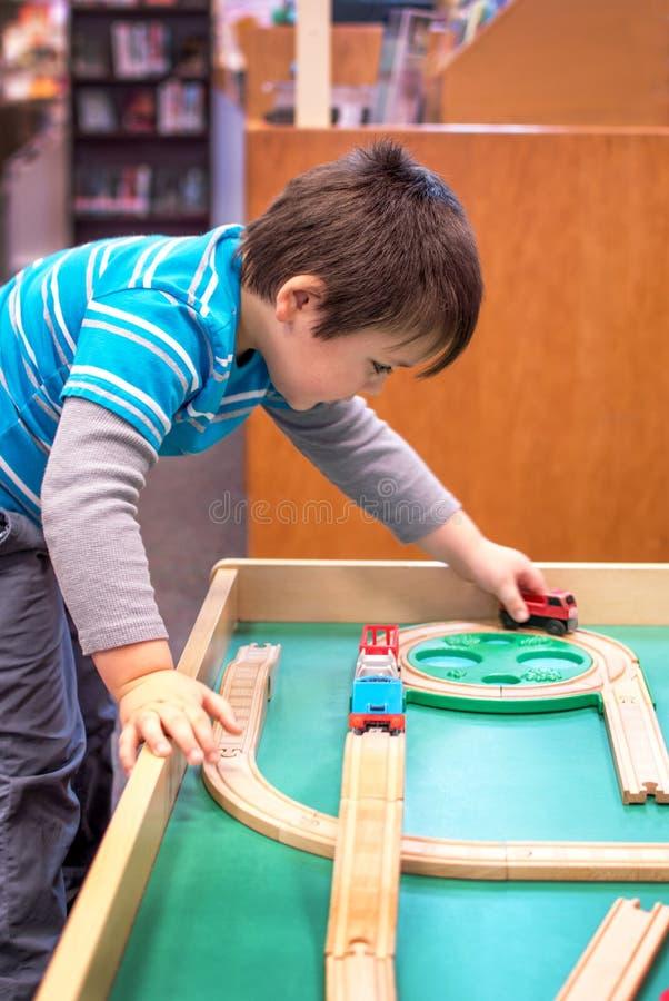 Glücklicher Junge mit Spielzeugzügen stockbilder