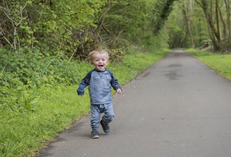 Glücklicher Junge mit zwei Jährigen, der draußen spielt und läuft stockfotos