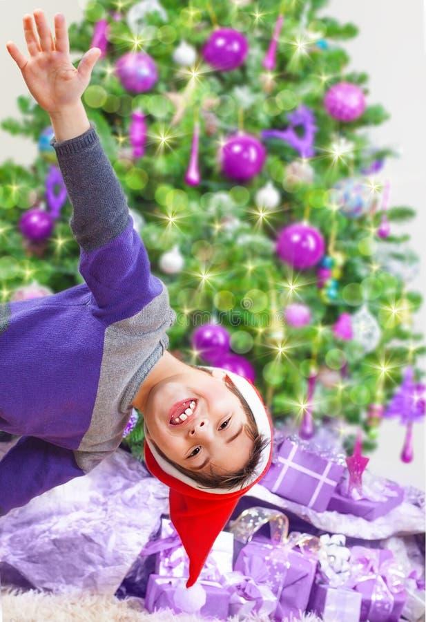 Glücklicher Junge nahe Weihnachtsbaum stockbild
