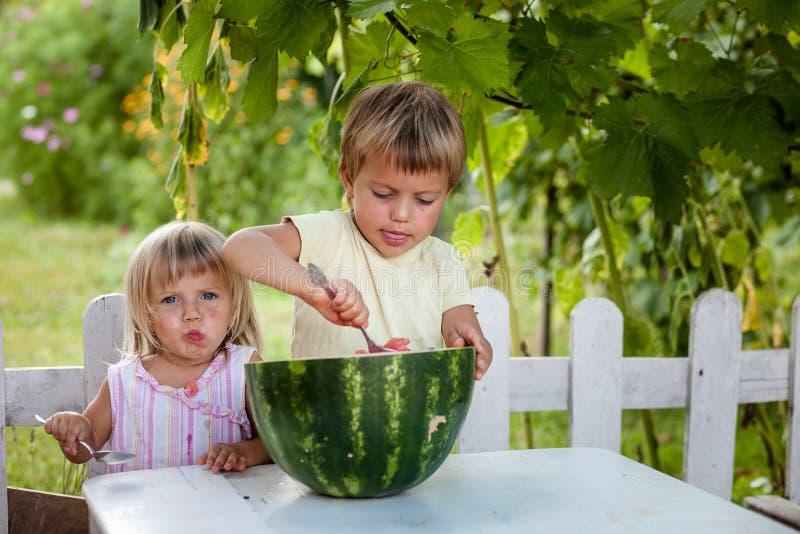Glücklicher Junge und kleines Mädchen mit dem Wassermelonenlügen stockbilder