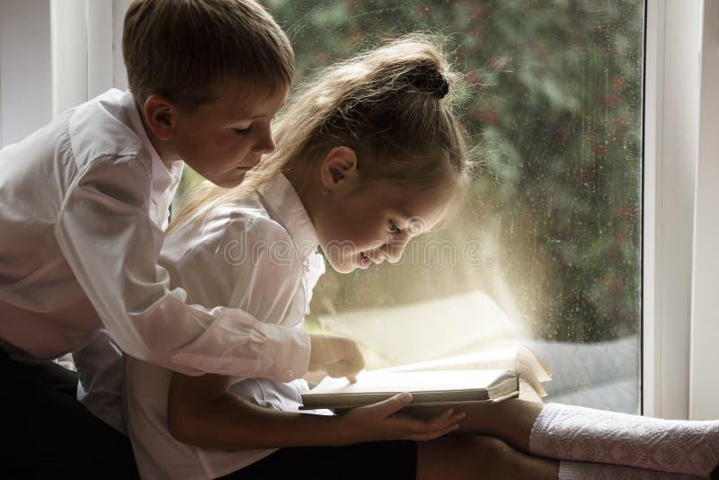 Glücklicher Junge und Mädchen, die auf den Fensterbrettlesebüchern auf Th sitzt stockbilder