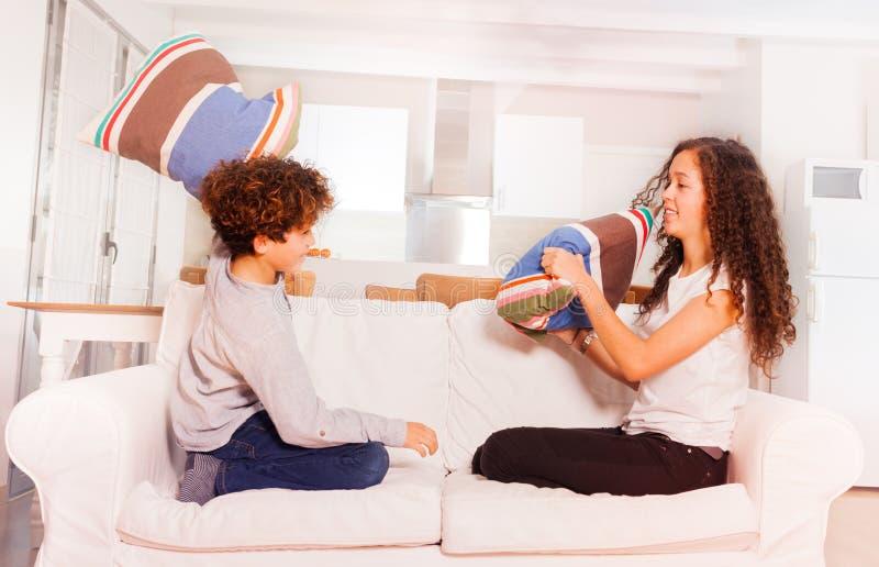 Glücklicher Junge und Mädchen, die zu Hause mit Kissen kämpft stockfotos