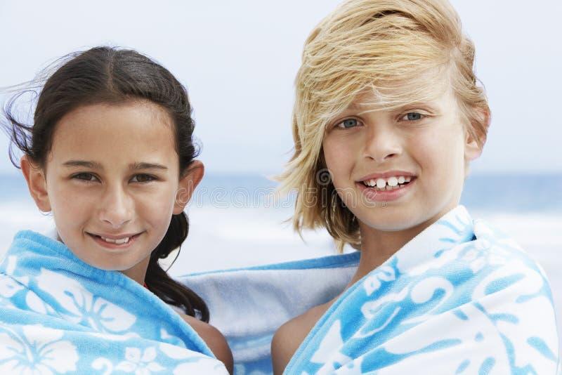 Glücklicher Junge und Mädchen zusammen eingewickelt im Tuch am Strand lizenzfreies stockfoto