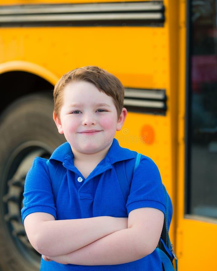 Glücklicher Junge vor Schulbus stockbild