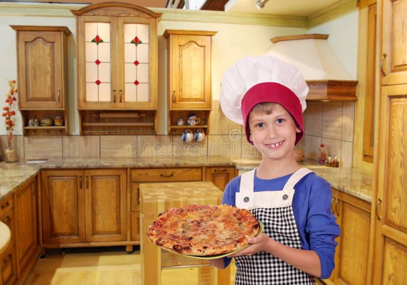 Glücklicher Jungenchef mit Pizza lizenzfreie stockfotos