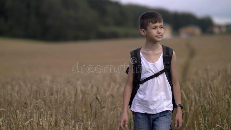 Glücklicher Jungenreisender mit einem Rucksack auf einem Weizenfeld im Dorf stockbild