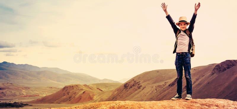 Glücklicher Jungenreisender mit seinen Händen wehrt sich auf dem Berg gegen den Himmel stockfotos