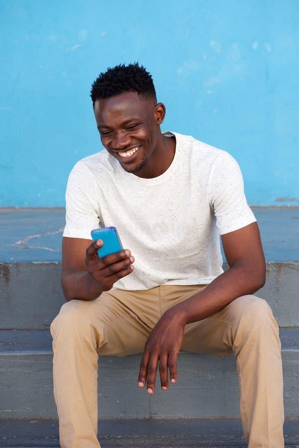 Glücklicher junger afrikanischer Mann, der auf Schritten sitzt und Telefon verwendet lizenzfreies stockfoto