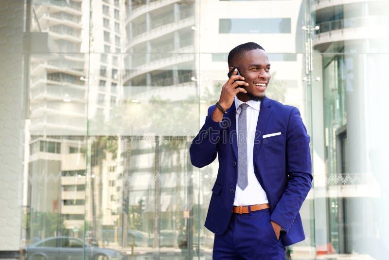 Glücklicher junger Afroamerikanergeschäftsmann mit Handy lizenzfreie stockbilder