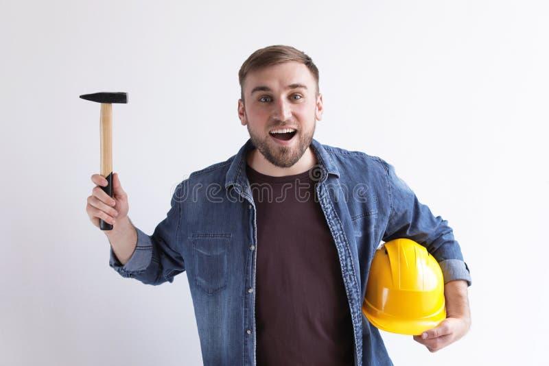 Glücklicher junger Arbeiter mit Hammer und Hardhat stockfotos
