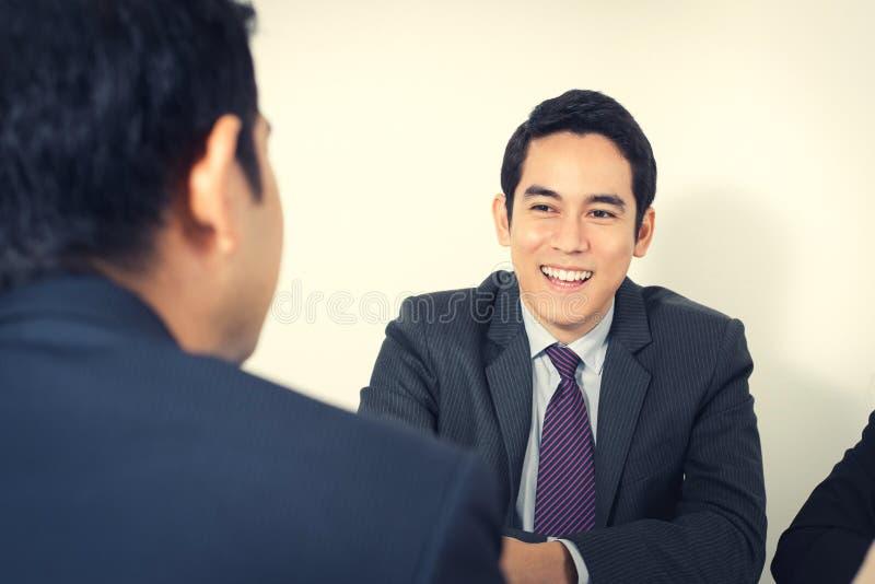 Glücklicher junger asiatischer Geschäftsmann in der Sitzung lizenzfreies stockbild