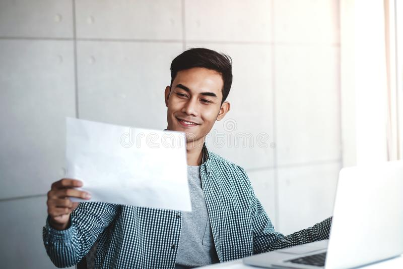 Glücklicher junger asiatischer Geschäftsmann Working auf Computer-Laptop an seinem Arbeitsplatz lizenzfreie stockbilder