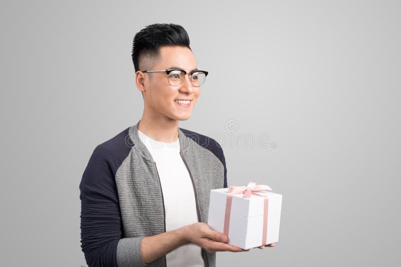 Glücklicher junger asiatischer Mann, der Geschenkbox über grauem Hintergrund gibt lizenzfreies stockfoto
