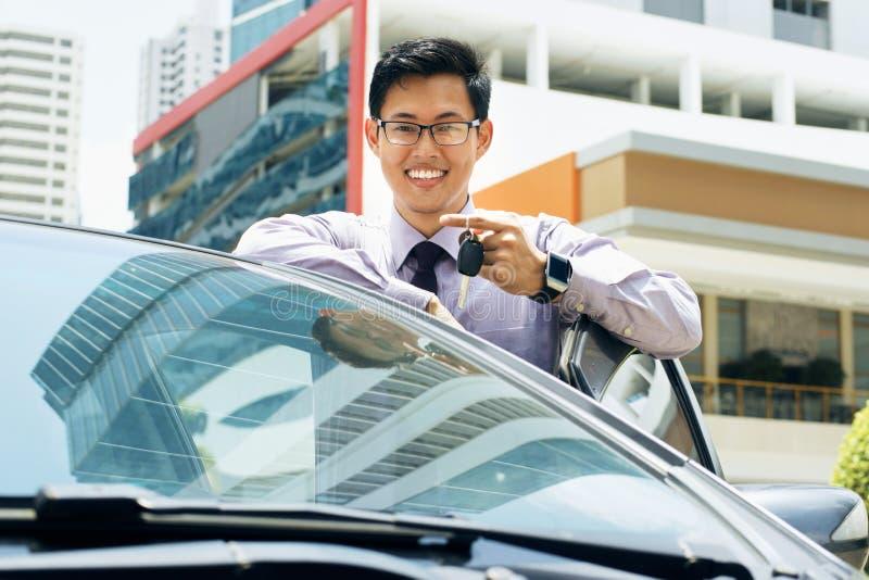 Glücklicher junger asiatischer Mann, der Schlüssel des Neuwagens zeigend lächelt stockfoto
