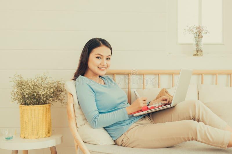 Glücklicher junger asiatischer Unternehmer, der zu Hause mit einem Laptop arbeitet lizenzfreie stockfotos