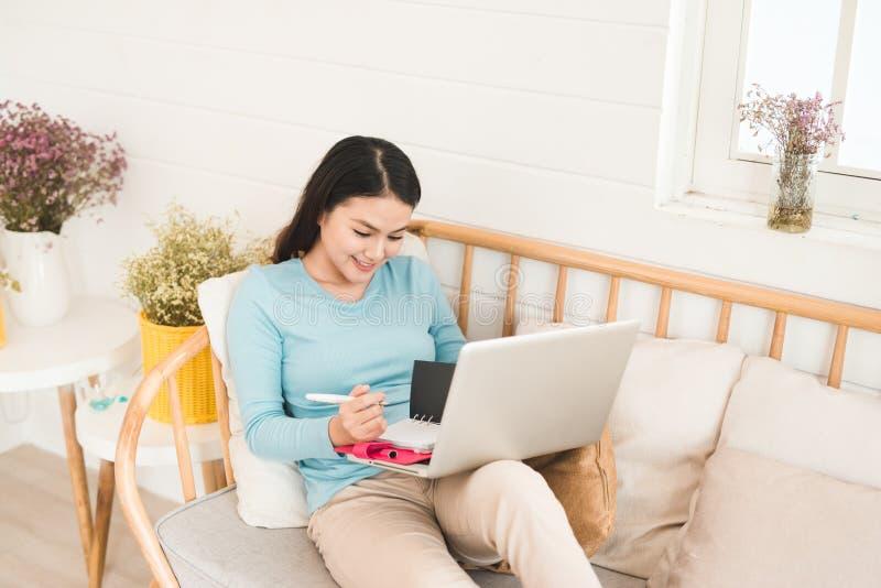 Glücklicher junger asiatischer Unternehmer, der zu Hause mit einem Laptop arbeitet stockbild