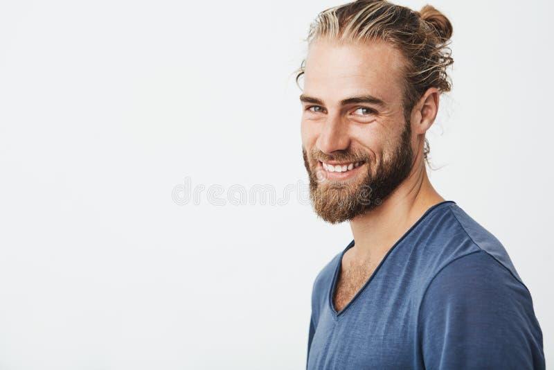 Glücklicher junger bärtiger Kerl mit moderner Frisur und Bart, der Kamera, brightfully lächelnd mit den Zähnen betrachtet und sin stockbilder