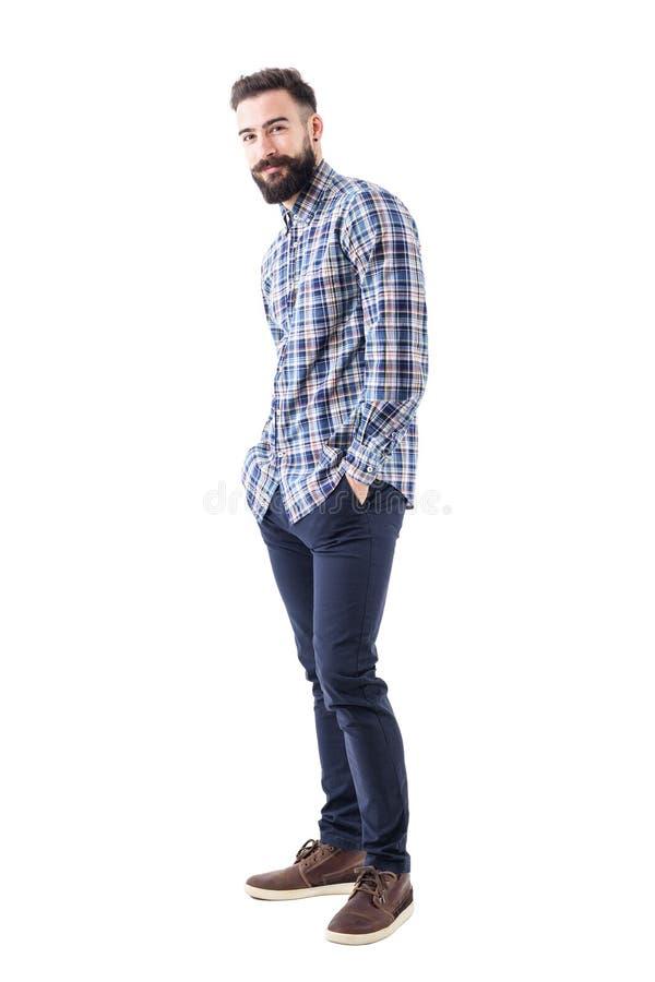 Glücklicher junger bärtiger Mann in überprüftem Hemd mit den Händen in den Taschen lächelnd und Kamera betrachtend lizenzfreie stockbilder