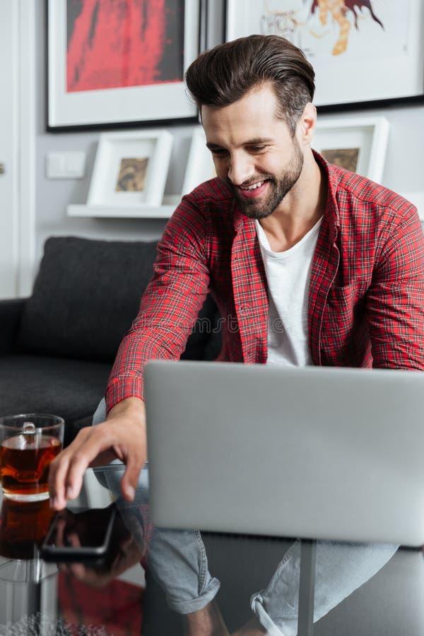 Glücklicher junger bärtiger Mann, der die Laptop-Computer hält Telefon verwendet stockfotos