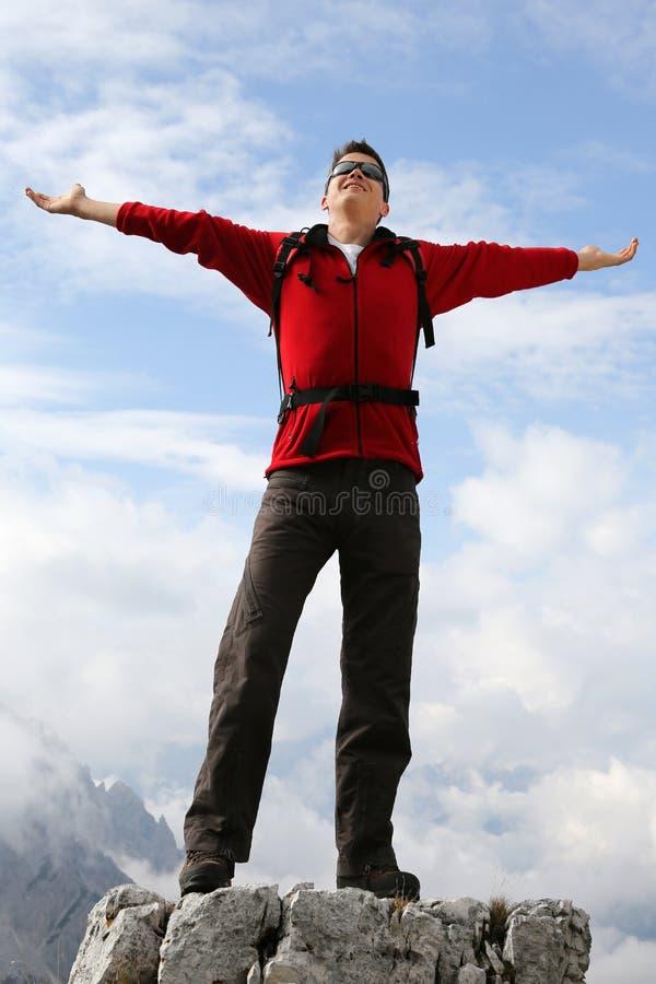 Glücklicher junger Bergsteiger auf Gebirgserfolgsthema lizenzfreie stockbilder