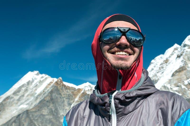Glücklicher junger Bergsteiger in der Sonnenbrille und in der Schutzkleidung stockbilder