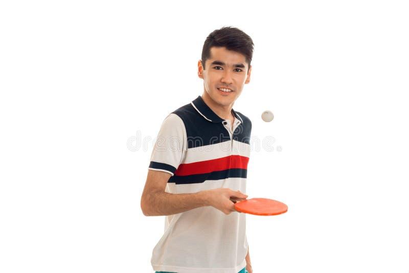 Glücklicher junger Brunettemann in übendem Tischtennis der Uniform lokalisiert auf weißem Hintergrund lizenzfreie stockfotografie