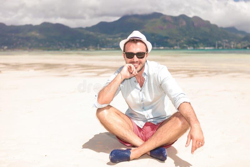 Glücklicher junger denkender Mann beim Sitzen auf Strand stockbilder