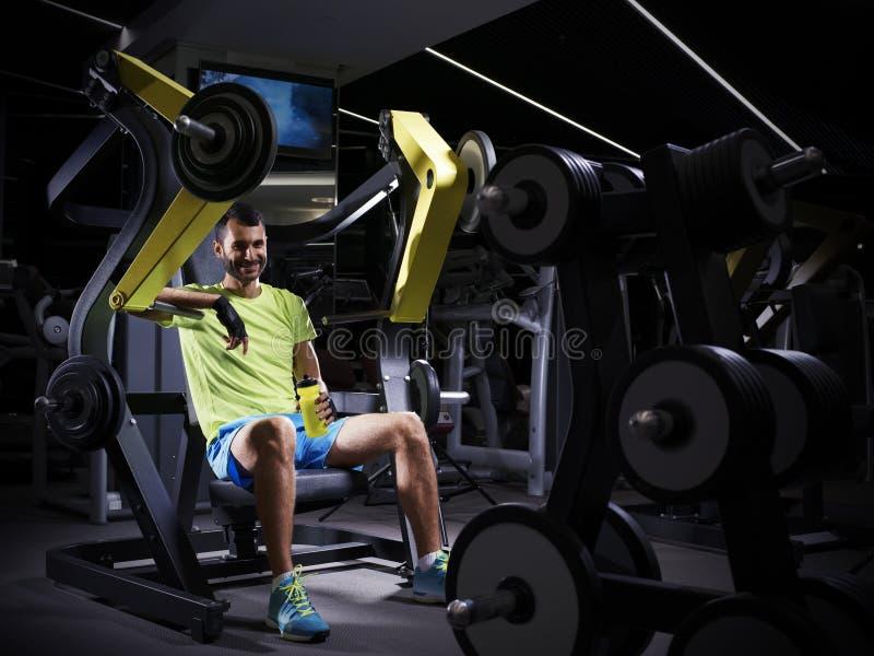 Glücklicher junger erwachsener Bodybuilder, der Gewichtheben in der Turnhalle tut lizenzfreies stockbild