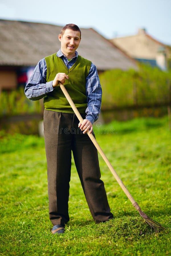 Glücklicher junger erwachsener Mann mit der Unfähigkeit, die im Frühjahr Garten bearbeitet stockfoto