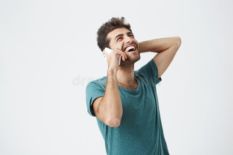 Glücklicher junger fühlender aufgeregt, glücklich und bei der Unterhaltung lachender Mann am Telefon Stilvoller Hippie, der mit s lizenzfreie stockbilder