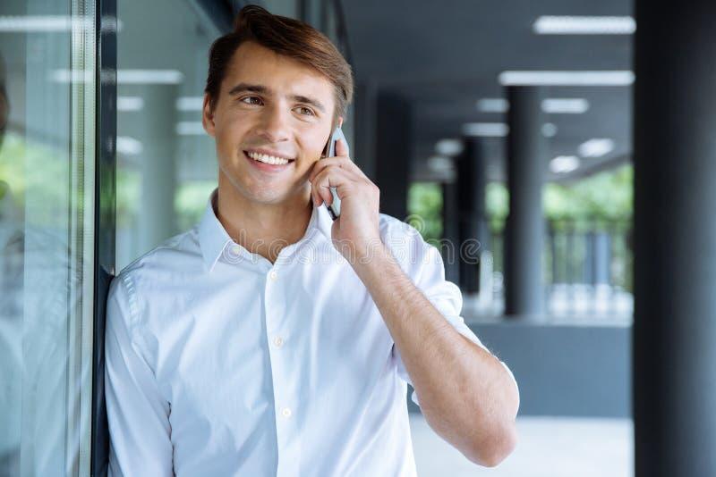 Glücklicher junger Geschäftsmann, der am Handy spricht stockfotos