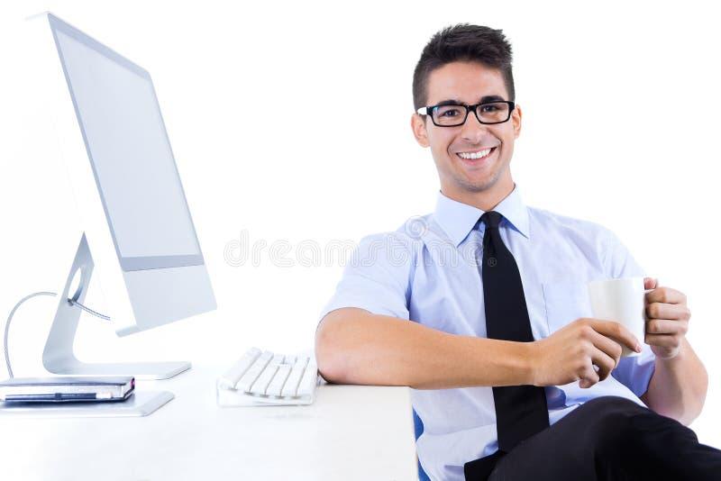 Glücklicher junger Geschäftsmann, der im modernen Büro sich entspannt stockfotografie