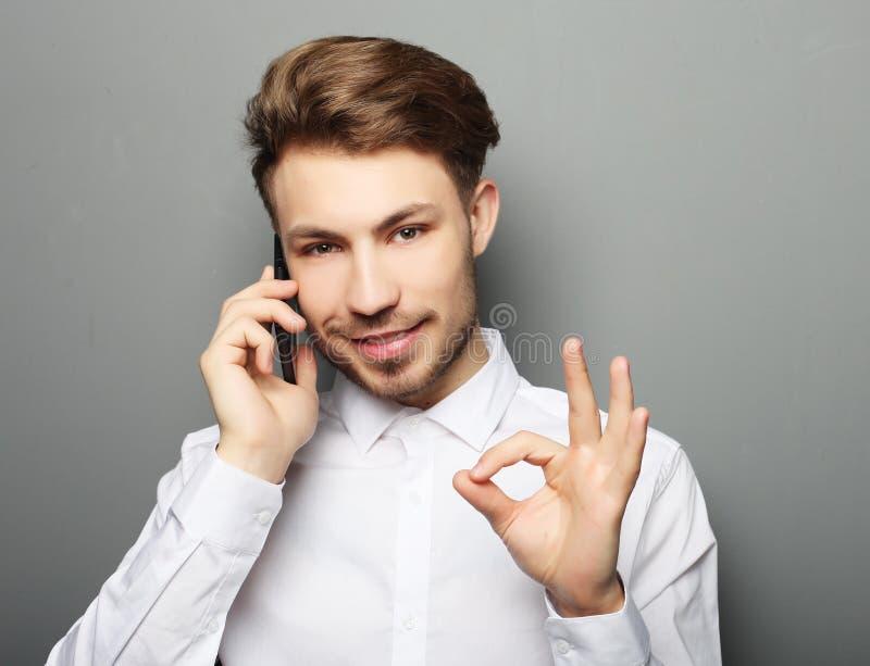 Glücklicher junger Geschäftsmann im Hemd gestikulierend und lächelnd während t stockbilder
