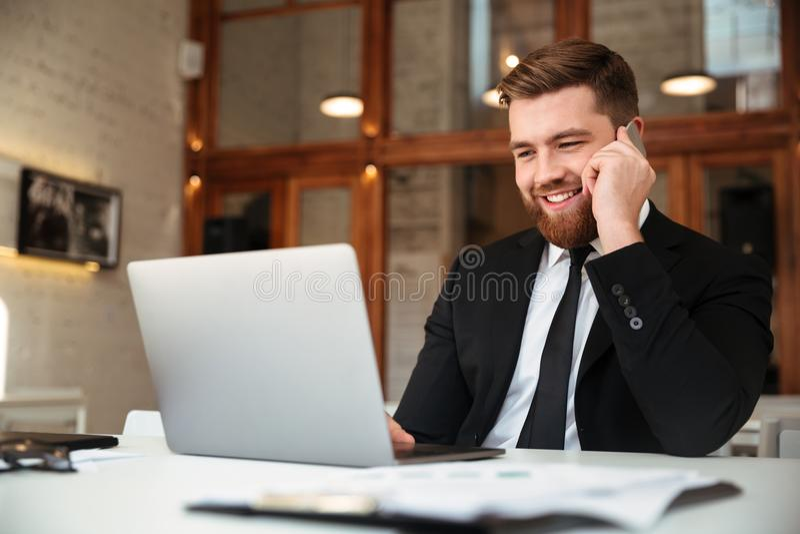 Glücklicher junger Geschäftsmann im schwarzen Anzug sprechend an Handy, L lizenzfreies stockbild