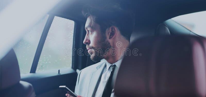 Glücklicher junger Geschäftsmann unter Verwendung des Handys im Rücksitz des Autos stockfotografie