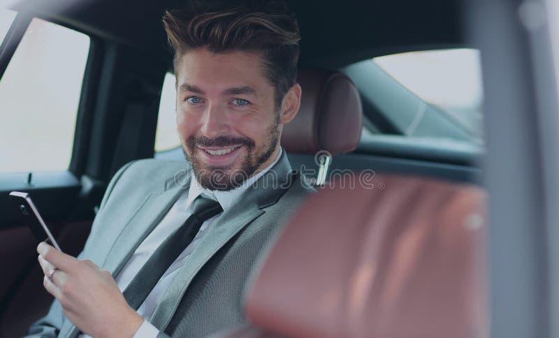 Glücklicher junger Geschäftsmann unter Verwendung des Handys im Rücksitz des Autos stockfoto