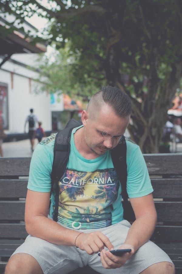 Glücklicher junger gutaussehender Mann, der draußen auf der Bank sitzt und Smartphone verwendet Tropeninsel von Bali, Indonesien stockbild
