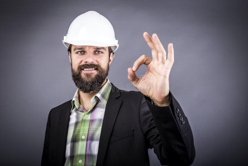 Glücklicher junger Ingenieur mit dem weißen Hardhat, der okayzeichen zeigt lizenzfreies stockbild