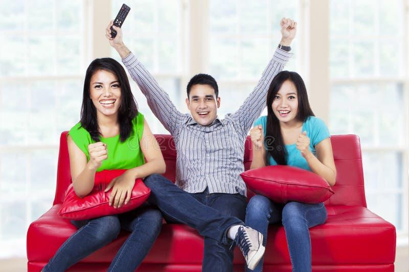 Glücklicher junger Jugendlicher, der zu Hause fernsieht stockbilder