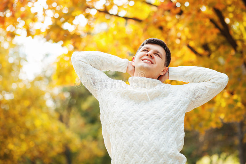 Glücklicher junger kaukasischer gutaussehender Mann, der im Herbstpark, im Ausdehnen und in rührendem Kopf bleibt Faule Herbsttag stockfotografie