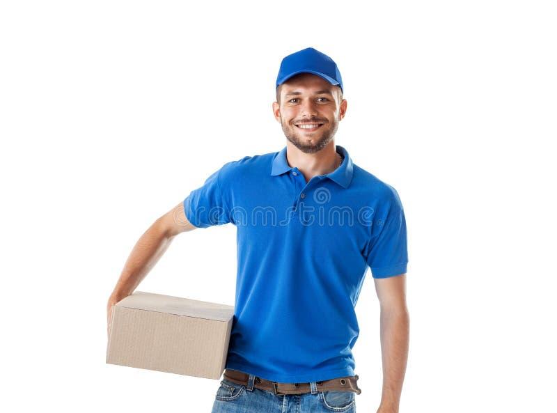 Glücklicher junger Lieferer in der blauen Uniform, die mit Paket PO steht lizenzfreie stockfotos