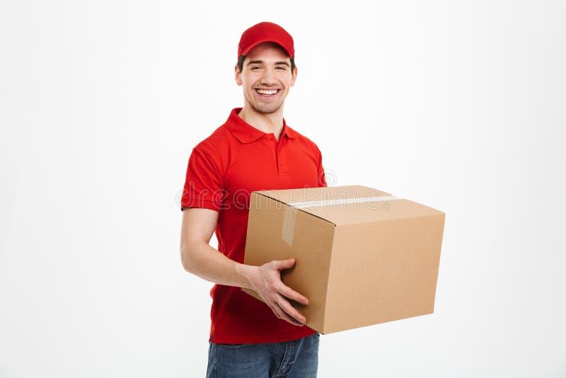 Glücklicher junger Lieferer mit Paketbriefkasten lizenzfreie stockfotos