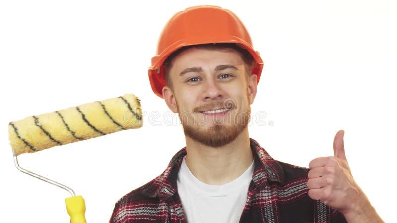 Glücklicher junger männlicher Erbauer, der die Farbenrolle sich zeigt Daumen hält lizenzfreie stockfotos
