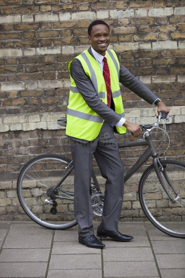 Glücklicher junger männlicher Ingenieur mit Fahrrad gegen Backsteinmauer lizenzfreie stockfotografie