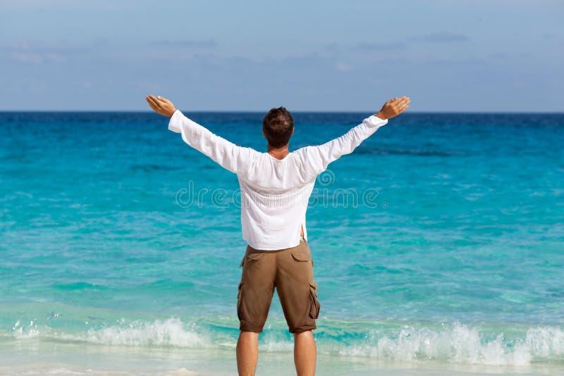 Glücklicher junger Mann auf dem Strand stockbild